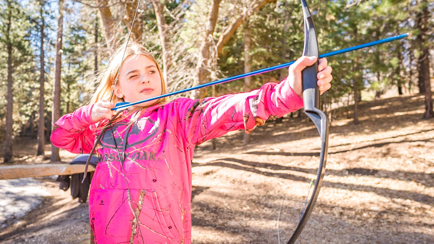 Girl in pink sweatshirt draws bow during Pali archery session