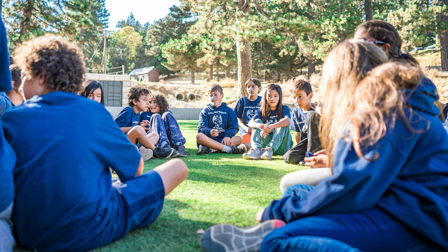 Pali students wearing blue shirts sit on grass outside