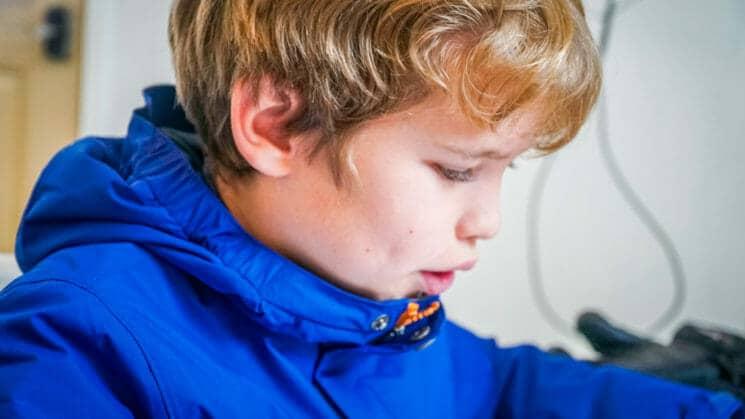 Close up of boy wearing blue jacket