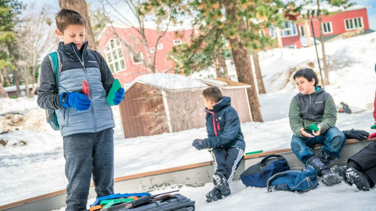 Boys hold colored puzzle pieces in snowy area