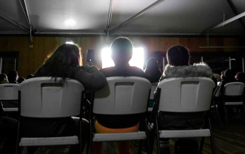 Chair backs of three students watching movie