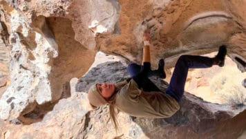 Pali staff member climbs inside of rocky cavern