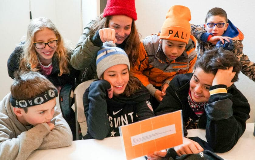 Excited group of Pali students look at orange clue card