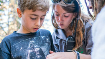 Pali Institute instructor helps student with compass