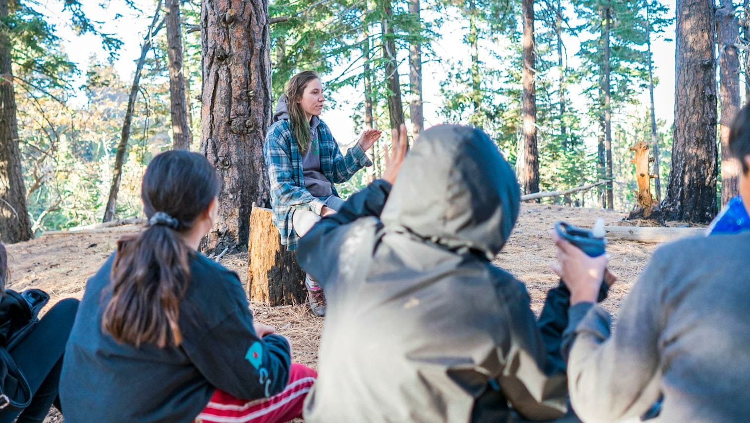 Pali instructor sits on log to address student group in woods
