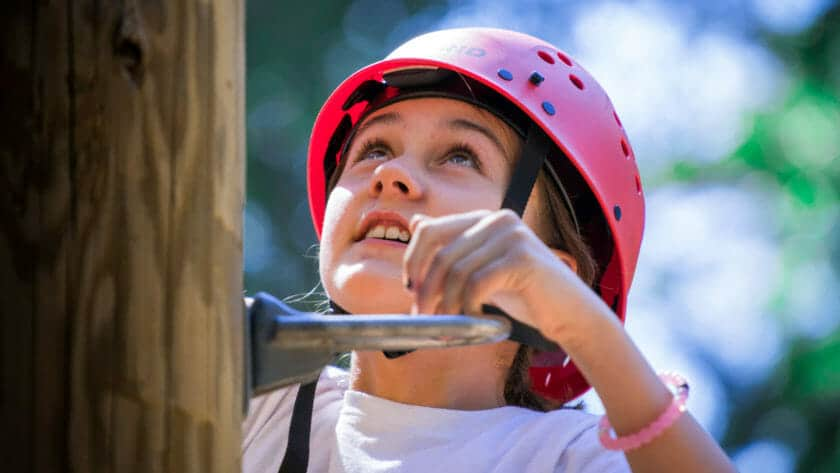 Close up of girl wearing helmet while climbing a pole