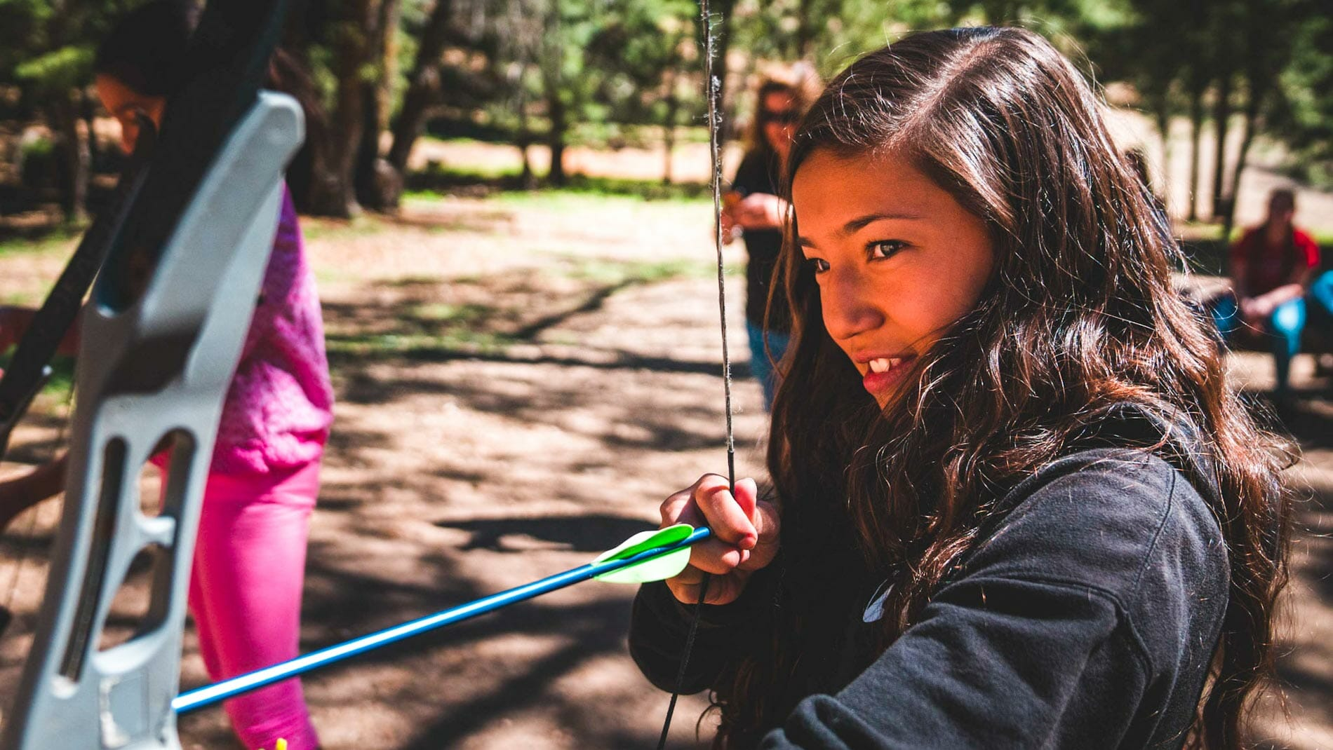 Girl drawing bow during Pali archery lesson