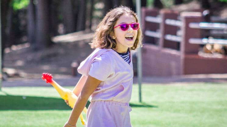 Girl in pink sunglasses hold squeaky chicken toy during Pali game