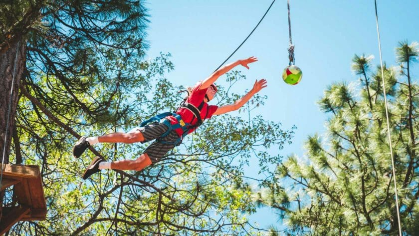 Pali student in harness jumps off high ropes course platform