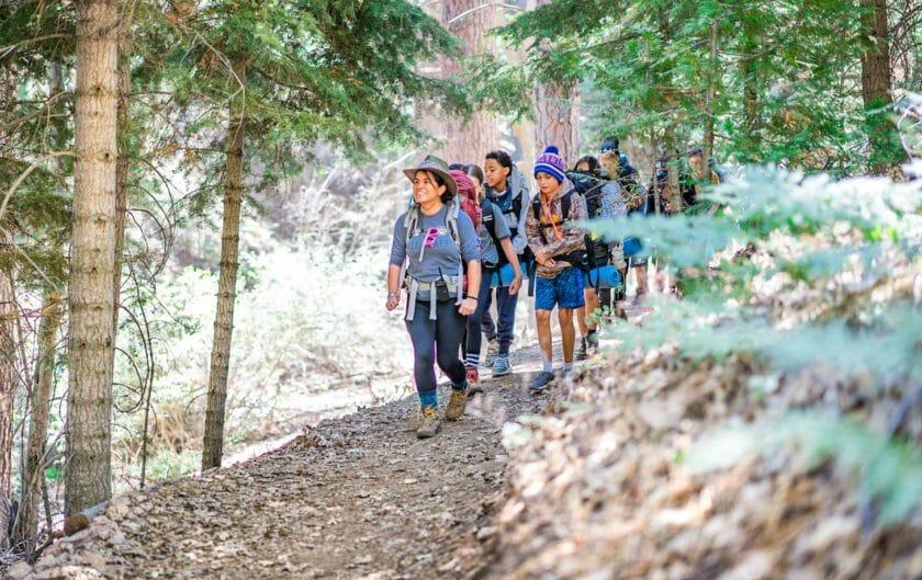 Pali hiking group walks down forest ledge trail