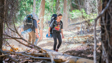 Pali student hikes past large branch in woods