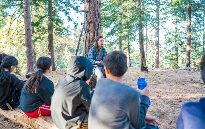 Pali instructor speaks to students seated on a log in woods