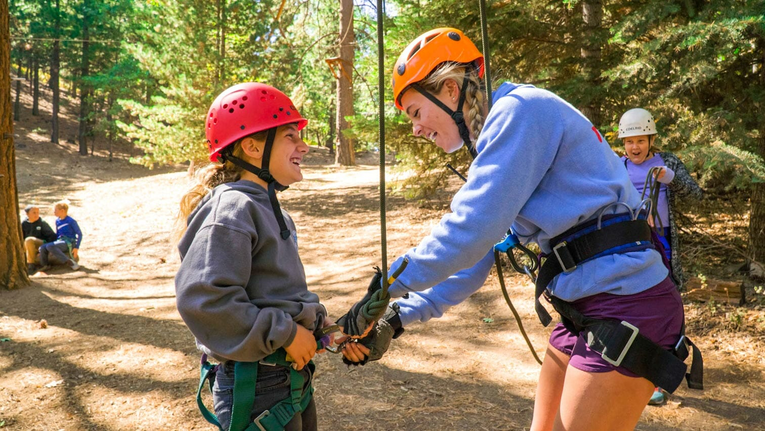Pali instructor helps student with ropes course harness