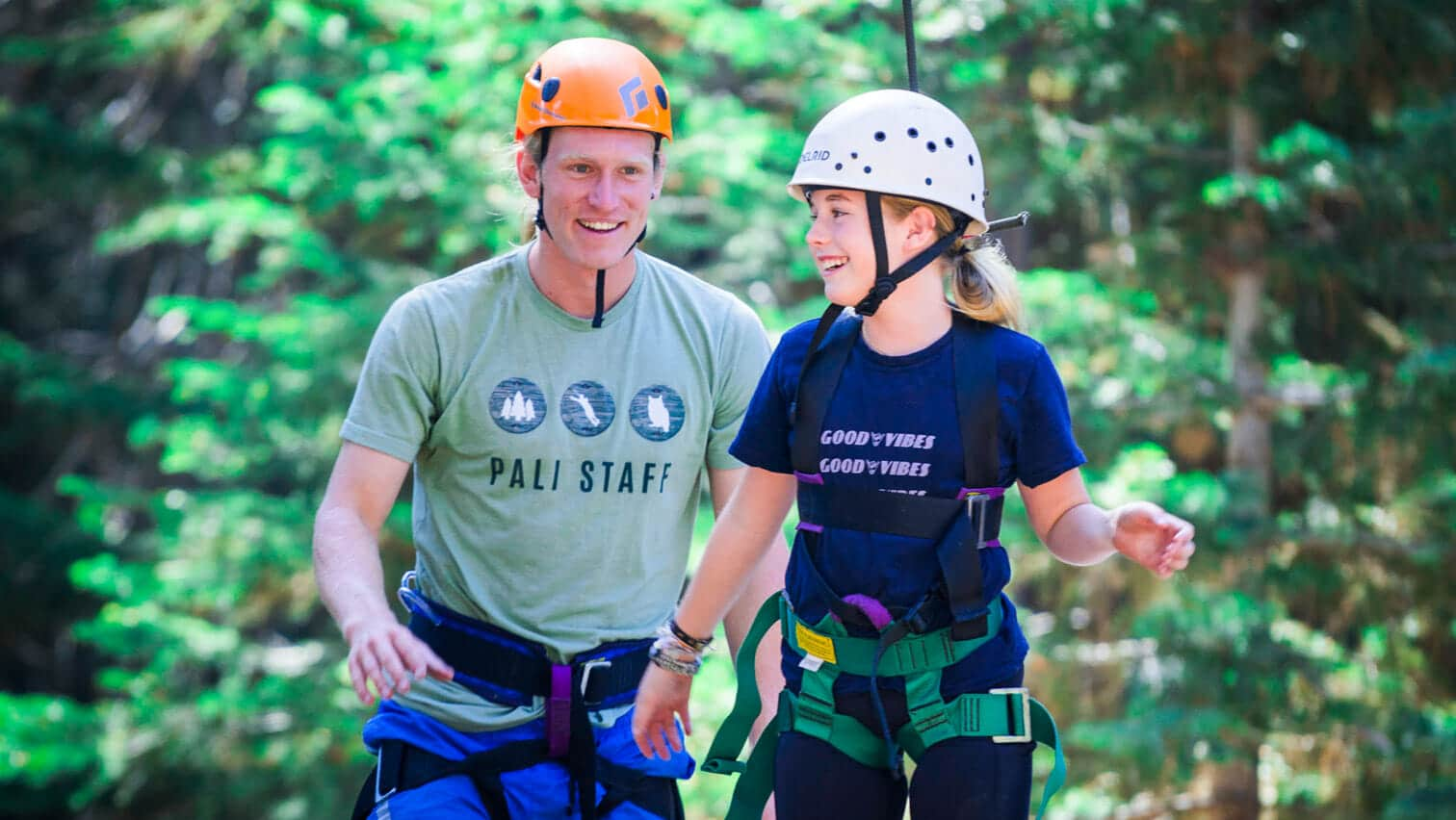 Pali instructor helps student across low ropes course