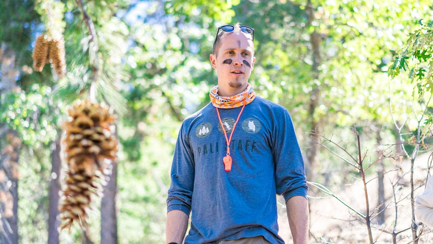 Pali instructor stands near hanging pinecones in woods