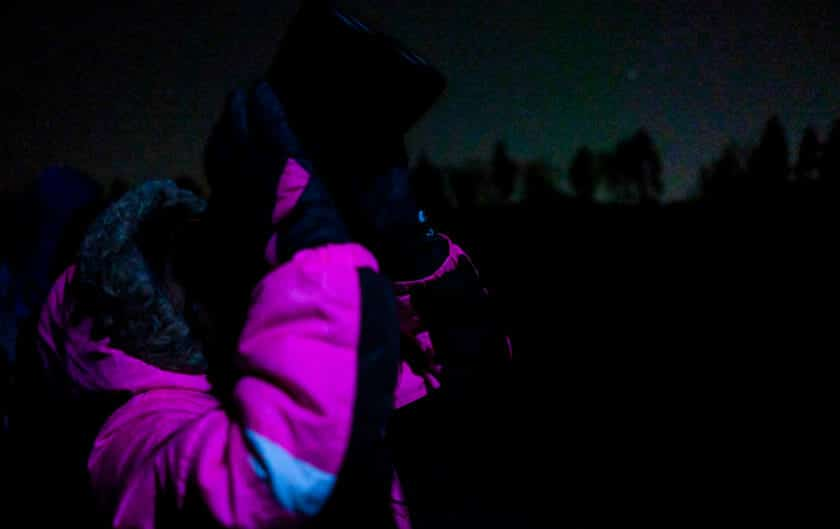 Student in pink jacket looks at night sky with binoculars