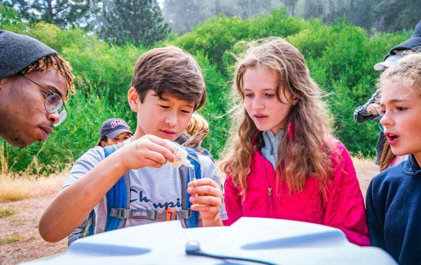 Student pours liquid into vial during outdoors Pali class