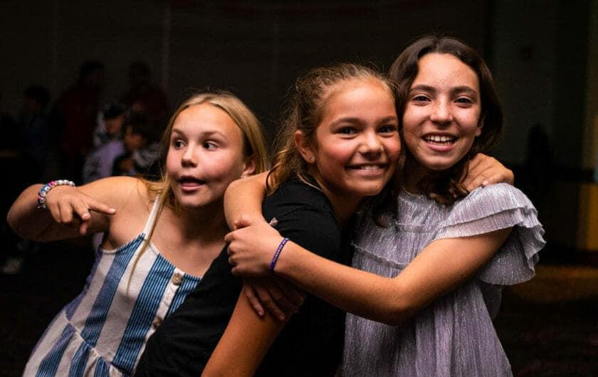Three girls smile during Pali Institute dance
