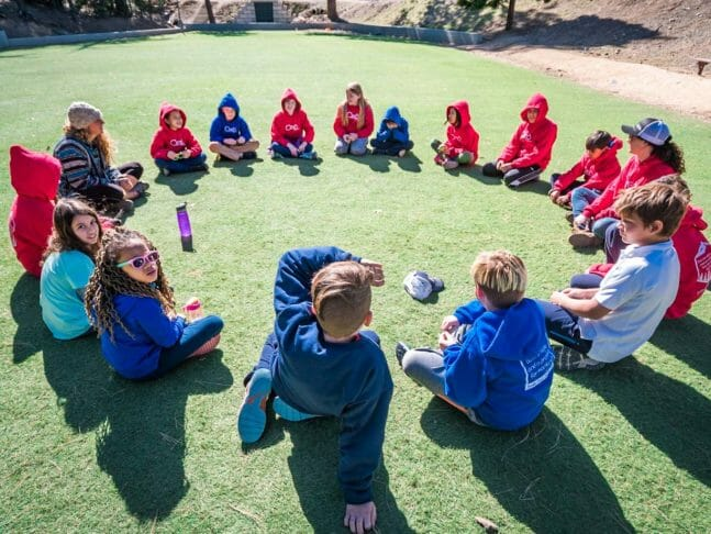 Group of pali students in blue and red sweatshirts sit in circle on grass