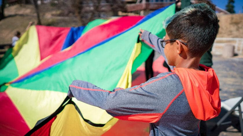 Young students holds edge of large colorful tarp
