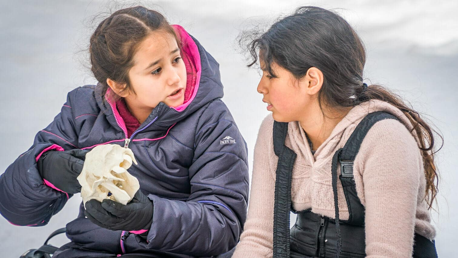 Two Pali students in snowgear sit outside and look at animal skull
