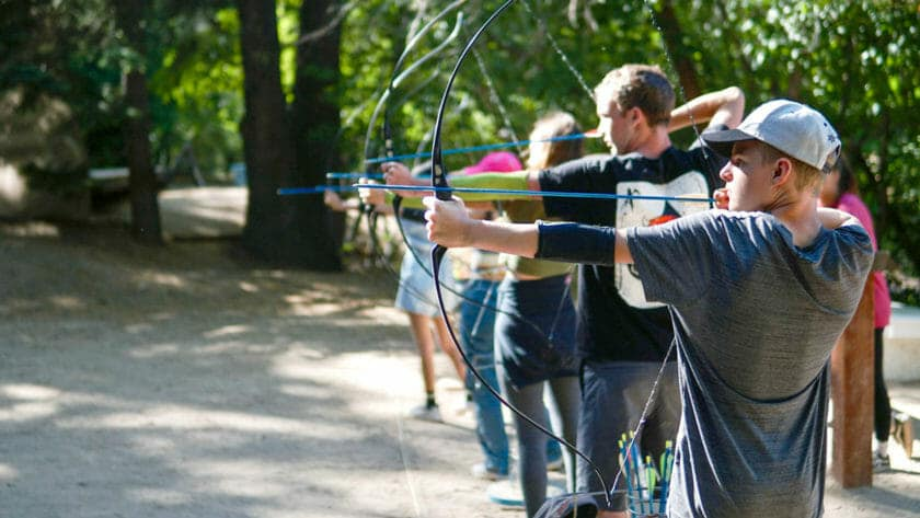 Line of Pali Institute students draw bows in archery lesson
