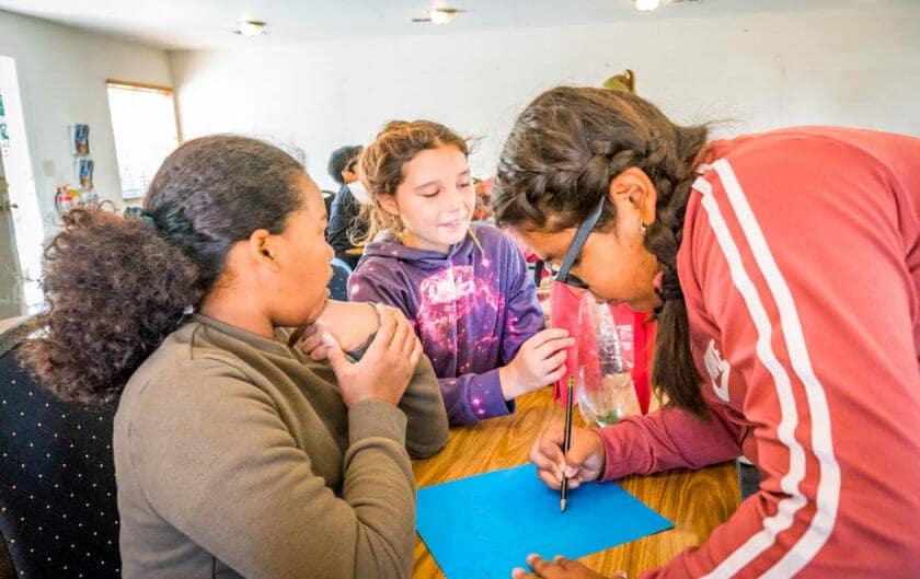 Students at Pali Institute work on bottle rocket blueprint