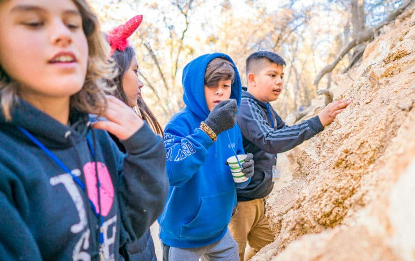 Pali Institute students inspect large rock in woods