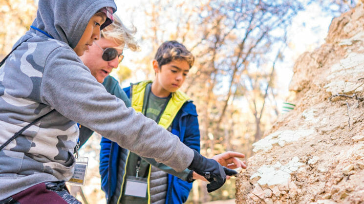 Pali Institute instructor shows students part of large rock in woods