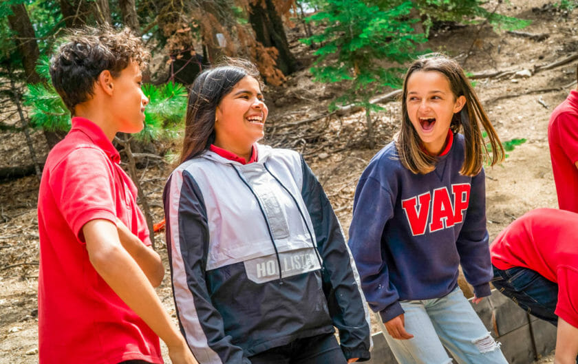 Three students laugh together at Pali Institute