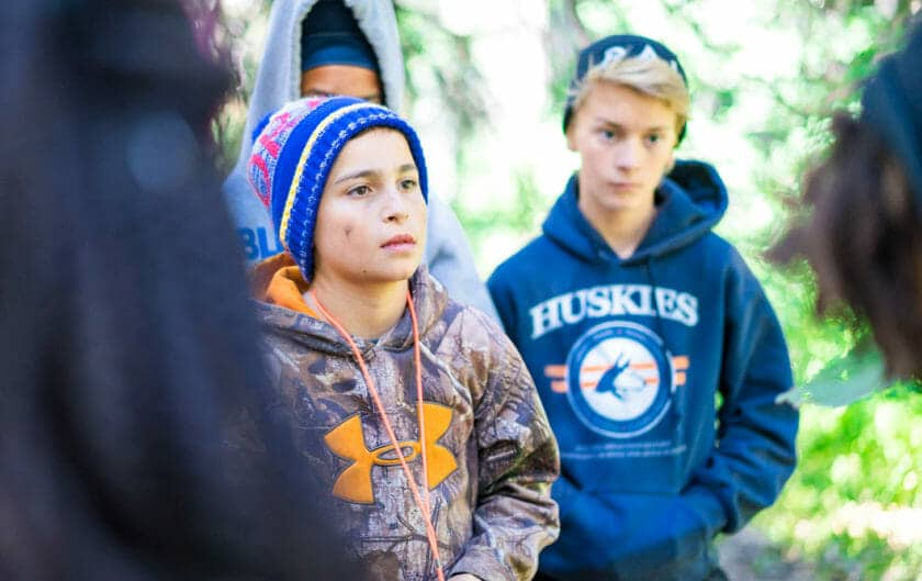 Students stand in woods during Pali orienteering class