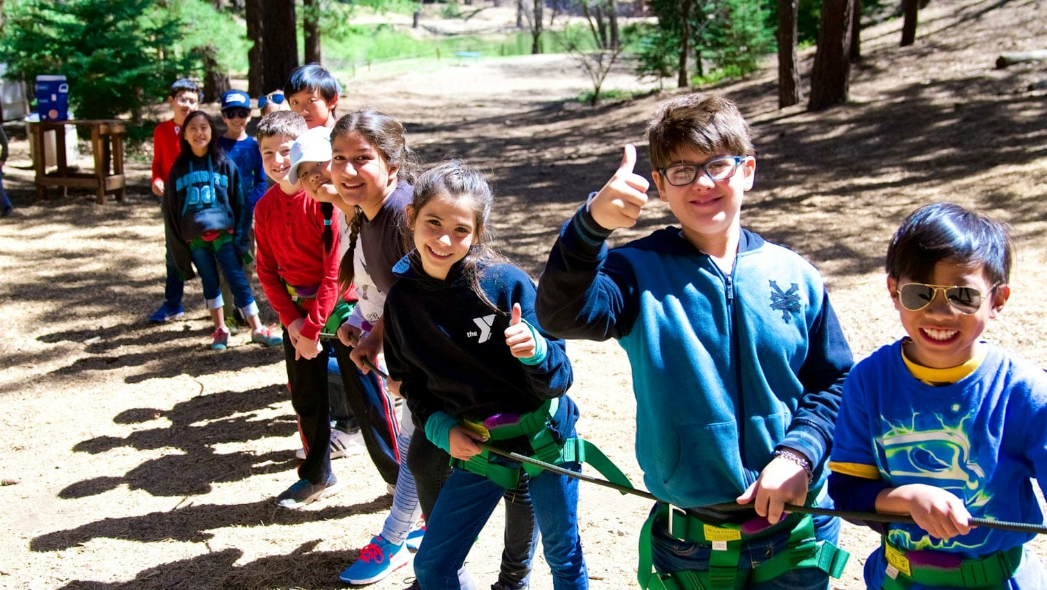 Students line up along rope while one gives thumbs up